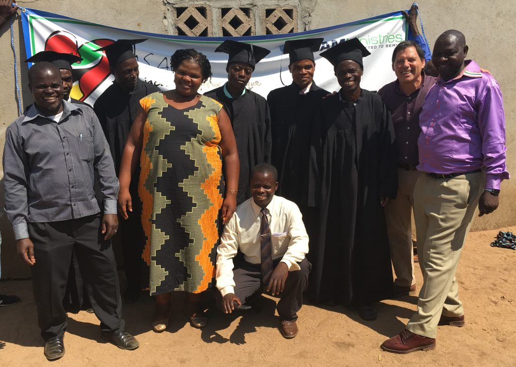 Guru graduates with the government official and Pastor Antonio, our monitor to her left.
