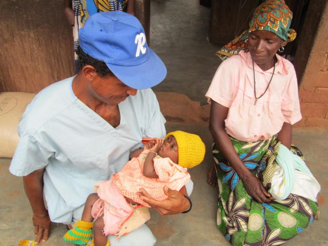 Health Worker Ernesto with granny and orphaned baby