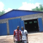 Prosper and Joao in front of the mission maintenance workshop
