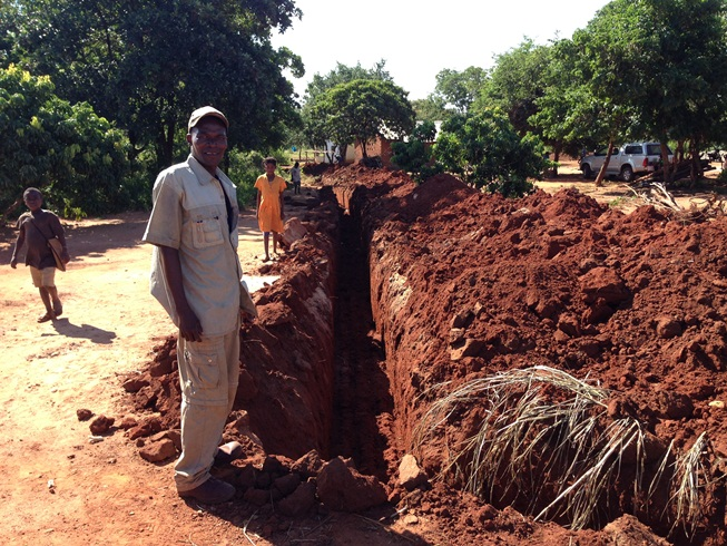 Tome our back hoe driver proudly showing his fine work! This is the trench from the clinic to the school kitchen.